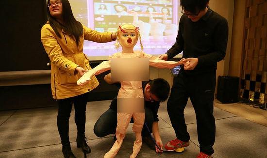 员工高兴地领取老干妈、充气娃娃等年终奖品。