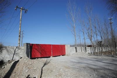 昨日,102国道段甲岭镇十百户路口东侧,此前院内堆得冒尖的石料(小图)已经被运走,院子大门紧闭。