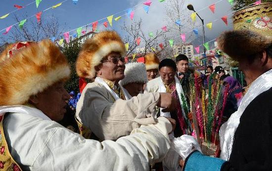 """2015年2月19日,拉萨西郊安居苑的藏族同胞欢聚在一起,相互敬献""""切玛""""、哈达,共同庆祝藏历新年,图片来源:新华网"""