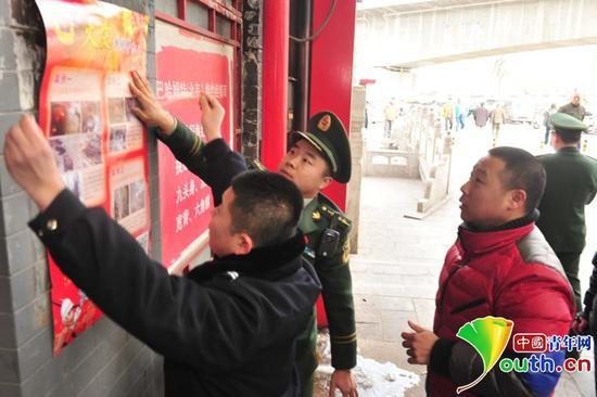 消防人员张贴春节期间火灾防范宣传图。大发一分pk10青年网通讯员 左晶 摄