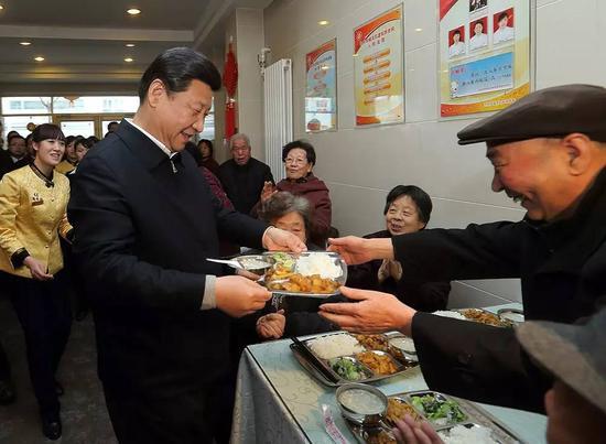 """2013年2月4日,习近平来到兰州一家""""虚拟养老院""""的养老餐厅,端起一个盛满饭菜的餐盘,走到72岁的老人杨林太面前,轻轻送上,请他用餐。新华社记者 兰红光 摄"""