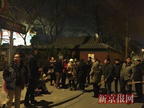 大年初一零点,雍和宫门口,已经排有超过50名香客,最前面的湖北人王先生以孙悟空造型装扮,和众人合影。新京报记者 赵力 摄