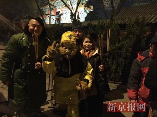 小年月朔零点,雍和宫门口,曾经排有超越50名香客,末了面的湖北人王老师以孙悟空外型打扮,和世人合影。新京报记者 赵力 摄