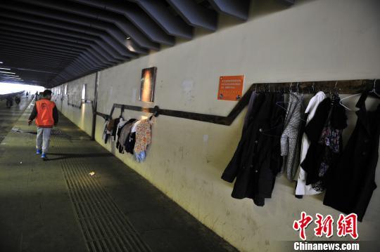 """刚被取缔的北站隧道""""爱心墙""""又挂上了衣服。 刘冉阳 摄"""