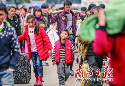 15日,广州火车站持续迎来旅客返程高峰,孩子帮忙拉着行李走出火车站。南方日报记者 张由琼 摄