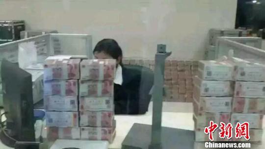 邯郸市一农村信用社营业网点内,办公桌上堆满了现金。 网络截图 摄