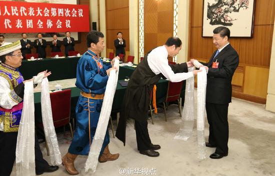 2016年3月10日,习近平参加十二届全国人大四次会议青海代表团的审议。这是少数民族代表向习近平敬献哈达