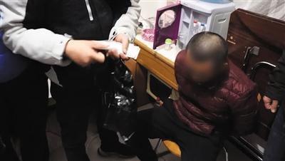 """专案组民警抓获一""""号贩子""""嫌疑人,民警手中拿着号贩子抢票所得的专家号。海淀警方供图"""