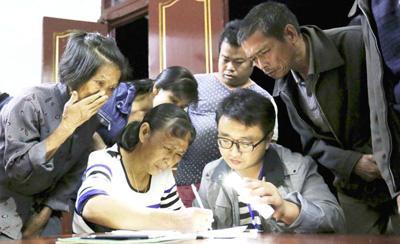 广西融安县大坡乡岗伟村第一书记陈中伟打亮手机,给村民讲解贫困户入户评估表。