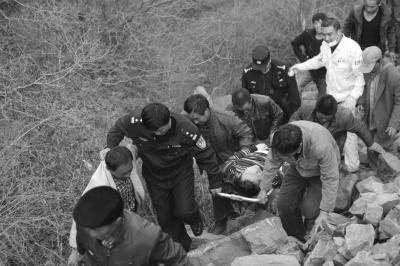 警民联手将伤者抬出山沟。