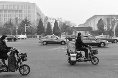 长安街上,一辆电动二轮车拉载大量货物。