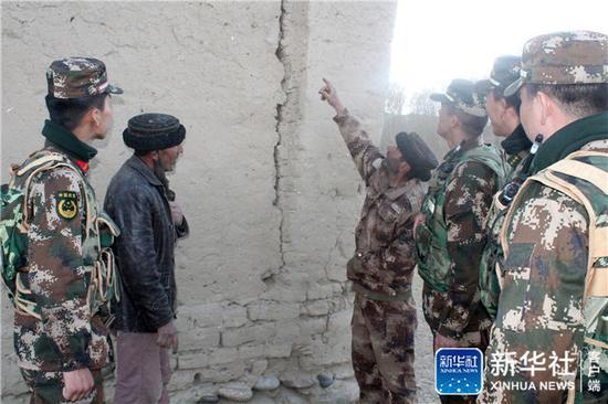 4月10日,武警新疆喀什边防官兵在边境辖区了解群众房屋受损情况。新华社发(李党辉 摄)