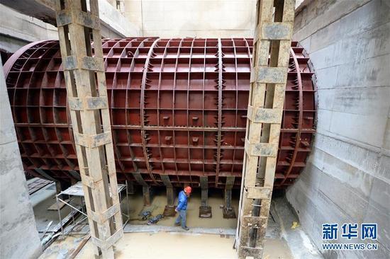 """5月9日,在黄河兰州段地面以下40米深处,施工人员查看地铁隧道口内部盾构机对外部钢套管的影响。当日,在黄河兰州段地面以下40米深处,中国铁建十四局集团""""金城四号""""盾构机从黄河北岸中间风井缓缓破洞而出,我国首条""""穿黄""""地铁——兰州地铁隧道1号线右线顺利贯通。兰州轨道交通成功穿越黄河河床、大堤等重大风险源,为年底全线洞通奠定了基础。新华社记者 范培珅 摄"""