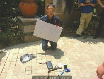 """男子被挂上写有""""小偷""""的纸牌示众。"""