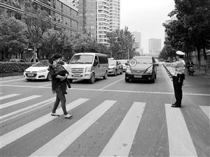 协警手持谦逊牌站在斑马线前揭示交往车辆 记者 吴依滢 摄