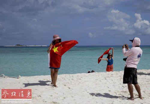 旅客举着五星红旗在全富岛照相纪念