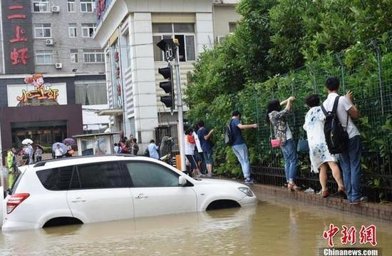 6月1日凌晨3时至上午10时,武汉市出现大到暴雨天气。据当地水务部门消息称,降雨中心位于江南地段,其中洪山、光谷地段降雨量达97-115毫米左右,全市20处地段出现渍水,多处道路被淹,不少轿车被困。目前,相关部门正组织抢排。图为渍水导致民众出行不便。 马芙蓉 摄