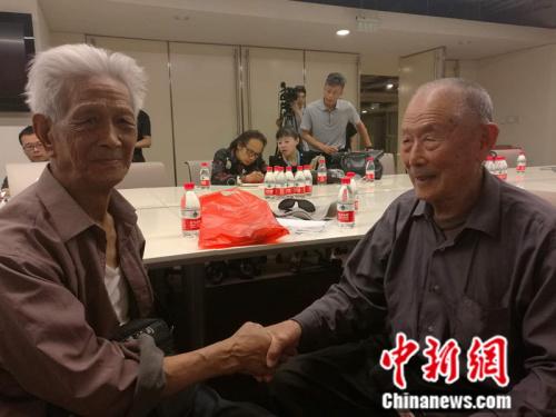 闫成全白叟(右)与另一位受害中国劳工赵宗仁握手。 张尼 摄