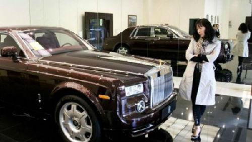 一位购物者端详一辆售价800万元人民币的劳斯莱斯幻影轿车。