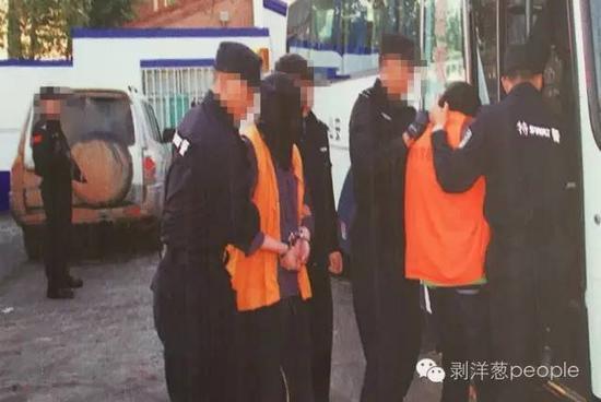 """乌拉特中旗公安局大厅展板上关于""""1.02""""案件中,押解犯罪嫌疑人的图片。新京报记者 尹亚飞 摄"""