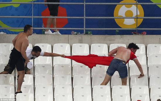一名俄罗斯球迷拉着一名英国球迷的衣服不放。