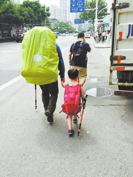 """6月14日,来自江西上饶的""""中国最小背包客""""雯雯随父亲来到成都。图为父女俩行走在蓉城街头。"""