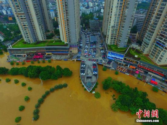 6月16日,因受暴雨影响,柳州呈现洪水围城的情景。图为航拍广西柳州市金沙角,船型建筑如在水中航行。 钟欣 摄