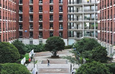 6月18日,昆明理工大学津桥学院,一名男生从事发的男生宿舍楼前走过。新京报记者 薛�B 摄
