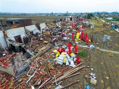 6月24日,阜宁县大楼村的房屋几乎被夷为平地,救援人员在帮助村民清理房屋。