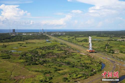 6月22日,承载着长征七号运载火箭与搭载载荷组合体的活动发射平台,从海南文昌航天发射场的垂直总装测试厂房驶出,平稳行驶约3小时后,安全转运至发射塔架。图为火箭垂直转运。中新社发 杨志远 摄