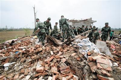 昨日,救援人员在帮助村民清理房屋。