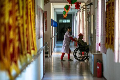 在一家敬老院,一名护理员用轮椅推着一名老人上电梯(2013年10月3日摄)。新华社记者刘金海摄