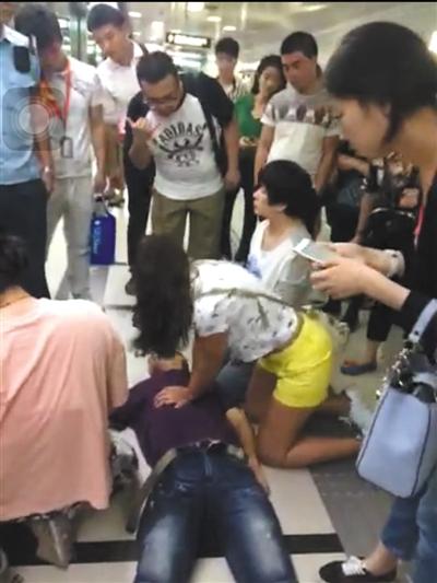 一位外籍女士志愿对倒地的金波进行心肺复苏。