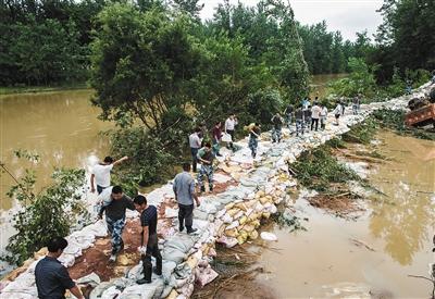 昨日,战士在新洲区沙河辛冲村段溃口处搬运防洪沙袋。目前已堵住溃口,正在加固。新华社记者 肖艺九 摄