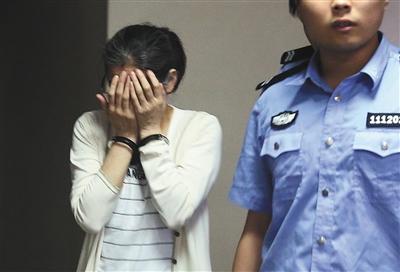 5月19日,庞建贞进入法庭前双手捂脸。庞建贞被法院一审认定伙同佟根柱受贿,获刑5年。资料图片/新京报记者尹亚飞摄
