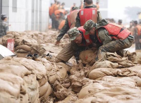 武警南京支队300名官兵在南京市鼓楼区三汊河持续奋战3天,搬运沙袋3万余袋
