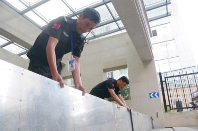 """7月8日,在温岭市万昌中路附近的一个小区门口,物业工作人员正在安装""""防洪神器""""。 网络图片"""