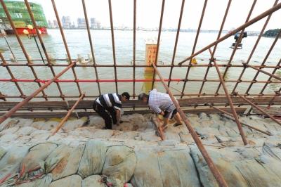 两位参与过1998年抗洪抢险的守堤人排查安全隐患。