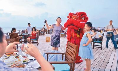 图为马尔代夫班多斯岛上,中国游客与舞狮合影留念。新华社记者 杨梅菊摄