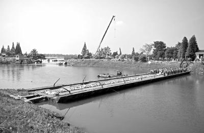 11日,湖南华容新华垸溃口附近已搭起浮桥,溃口两侧挖掘机、卡车轮番作业进行填堵,溃口正逐渐缩小。