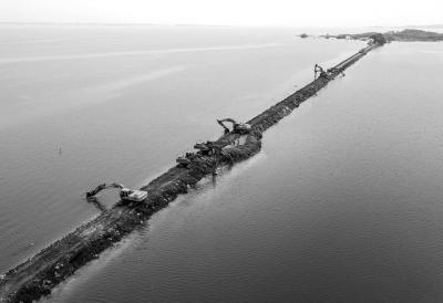 13日,武警水电第七支队的战士在牛山湖坝上进行破垸前的准备施工作业。新华社发