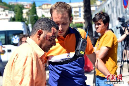 图为医护工作者在医院门前为一名恐袭伤者提供帮助。 中新社记者 龙剑武 摄