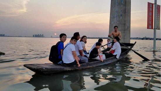 7月8日,武汉江夏大道被水淹没,与周围的汤逊湖连为一体,附近居民坐船回家。 摄影:俞琴