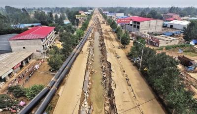 洪水将坑内的管道冲到路边。京华时报记者潘之望摄
