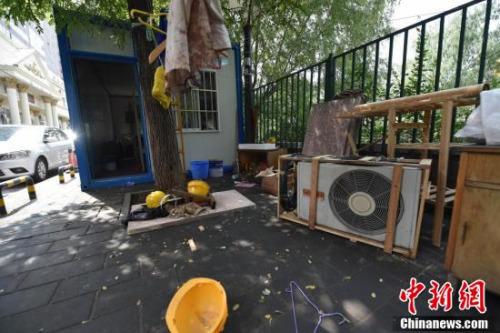 """图为""""柜子""""旁堆放的杂物和拆下来的空调。中新网记者 金硕 摄"""