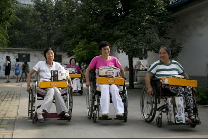 郑维芹与其他疗养者在参加完爱心仪式后推着轮椅回家,她落在了后面。中国青年网记者 孙钊 摄