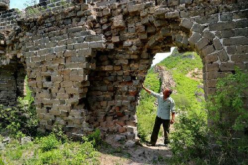 长城守望者张鹤珊在察看城子峪长城一座敌楼的伤残情况。