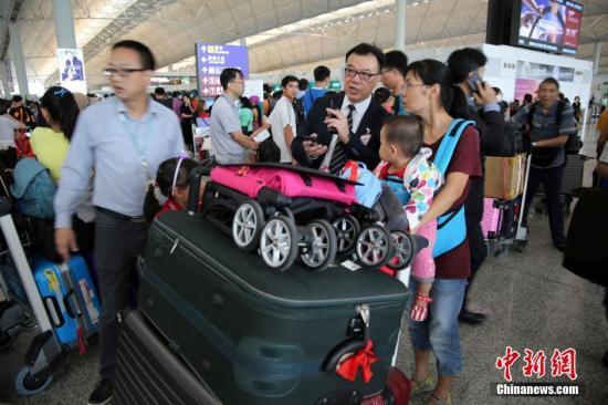"""8月2日,热带风暴""""妮妲""""袭港,天文台发出八号热带气旋警告信号,机场多班机受风暴影响,需要取消或延误,大批旅客滞留。中新社记者 洪少葵 摄"""