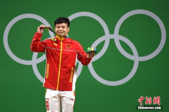 图为龙清泉展现奥运金牌。中新网记者 富田 摄