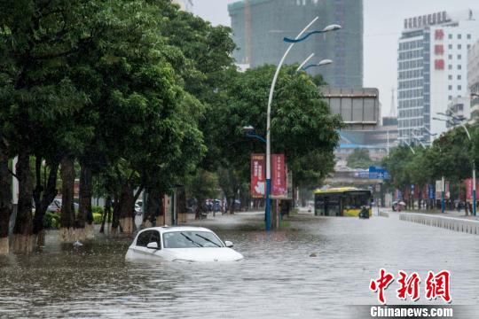 """受""""电母""""影响,海口市出现严重内涝,图为道路上被淹的小汽车。 洪坚鹏 摄"""